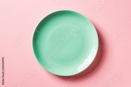 Foto  Green plate on pink background, from above