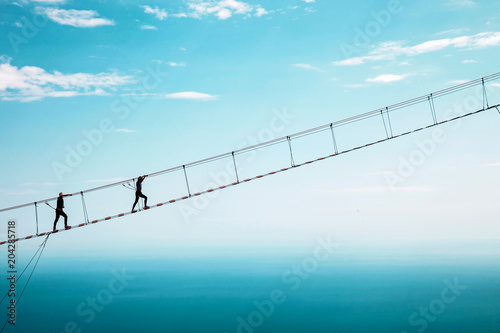 Young woman crossing the chasm on the rope bridge. Ai-Petri, Crimea