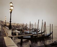 Gondolas Moored At A Waterfront, Venice, Italy.