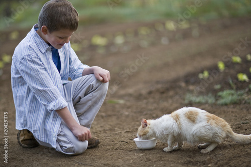 Young boy giving a cat a bowl of milk.