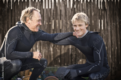 Portrait of a smiling young man wearing a wetsuit and with his arm around his father.