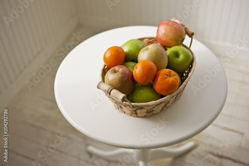 Basket of fresh fruit on a table inside a room.