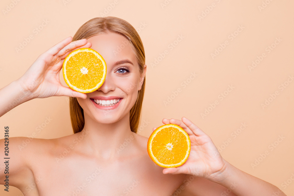 Fototapeta Pretty charming joyful attractive cheerful funny comic positive nude natural pure girl having two pieces of orange, closing one eye, isolated on beige background with copy space for advertisement