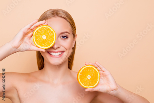 Fototapeta Pretty charming joyful attractive cheerful funny comic positive nude natural pure girl having two pieces of orange, closing one eye, isolated on beige background with copy space for advertisement obraz