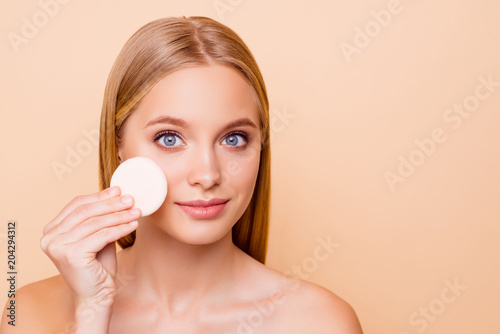 Pretty girl with problem oiled dry skin removing make up with cotton pad from cheek, daily, everyday care concept isolated on beige background with copy space, empty place, advertisement, concept