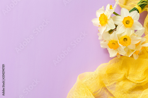 Deurstickers Narcis Daffodil bouquet with yellow textile decoration on violet pastel background with copy space.