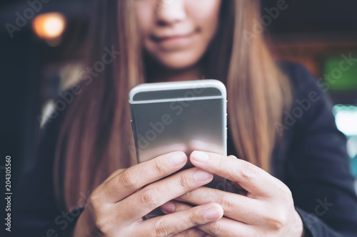 Fotografía  Closeup image of a woman holding , using and looking at smart phone