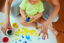 The Mother With Son Painting A Big Paper By Hands