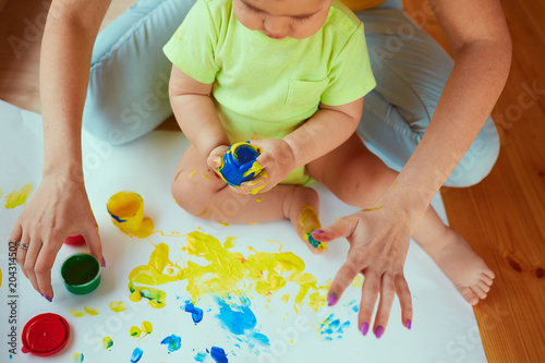 The mother with son painting a big paper by hands Canvas Print