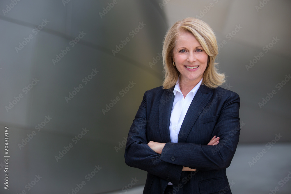 Fototapeta Confident and successful CEO business woman in a suit with arms folded