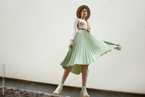 Young red hair girl in hat, dressed in beige blouse and turqoise pleats skirt, on light street backgraund Wallpaper Mural