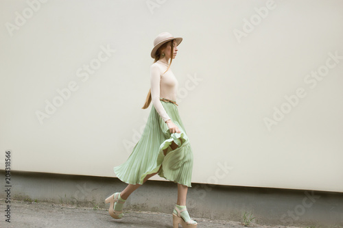Fotografia, Obraz  Young red hair girl in hat, dressed in beige blouse and turqoise pleats skirt, on light street backgraund