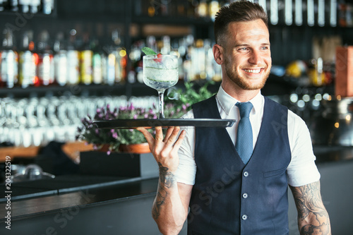 Photo Smiling waiter ready to serve a cocktail