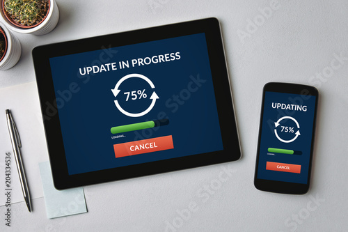 Fotografía  Update concept on tablet and smartphone screen over gray table