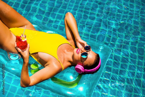 Poster Magasin de musique amazing beautiful girl in a yellow bikini air mattress swims in the pool of a luxury hotel, summer vacation, happiness, travel, smile joy, listening to music, drinking cocktail