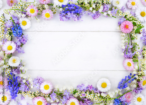 Foto op Canvas Bloemen Floral layout, creative flower composition. Wreath framefrom lilac and pink daisies on white wooden background, top view. Flat lay, copy space, macro.