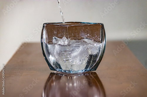 Fotografie, Obraz  water pouring over ice into square crystal vase