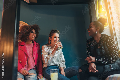 Group of three beautiful young multiracial women sitting in a coffee shop interacting