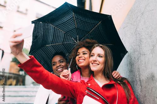Group of three beautiful young multiracial women having fun walking on the rain