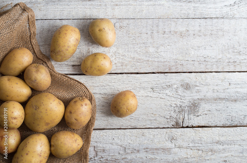 Fresh potatoes on an old wooden table