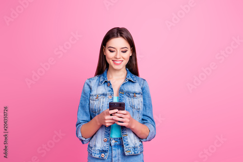 Fototapeta I use smiley faces to express my emotion in sms! Portrait of cute confident lovely attractive charming gorgeous girl watching video on phone, isolated on pink background obraz na płótnie