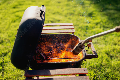Foto op Canvas Bier / Cider Gas torch is being used to light up the coal inside the grill on field.
