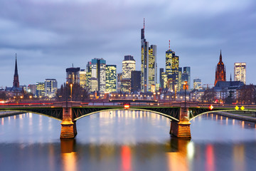 Obraz na Szkle Miasta Picturesque view of Frankfurt am Main skyline and Ignatz Bubis Brucke bridge during evening blue hour with mirror reflections in the river, Germany