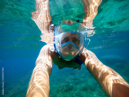 Underwater view of a young diver man swimming in the turquoise sea under the surface with snorkeling mask for summer vacation while taking a selfie with a stick.