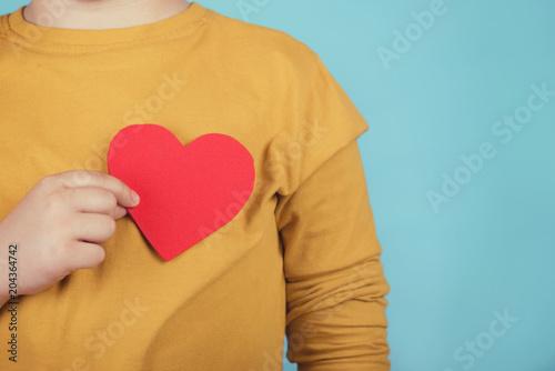 Photo niño con un corazón sobre fondo azul