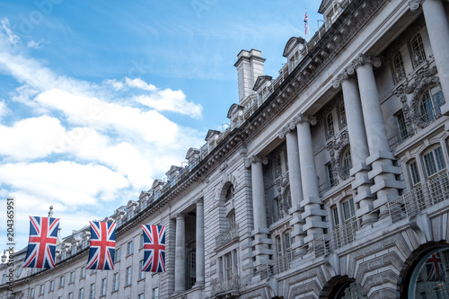 Fotomural Close up of buildings on Regent Street London UK photographed from street level, with row of British flags to celebrate the Royal Wedding of Prince Harry to Meghan Markle