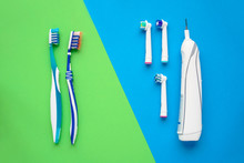 Electric And Manual Toothbrushes. Top View. Hygiene Of The Oral Cavity. An Ordinary Toothbrush And Electric Toothbrush On Bright Green And Blue Background.