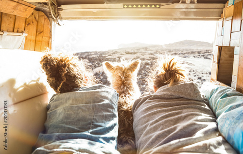 Hipster couple with cute dog traveling together on vintage van transport - Life inspiration concept with hippie people on minivan adventure trip watching sunset in love moment - Warm sunshine filter