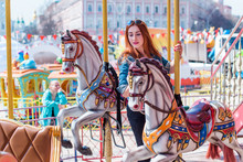 Adult Girl Has Fun On The Carousel And Has A Good Time. The Concept Of Fun In The City