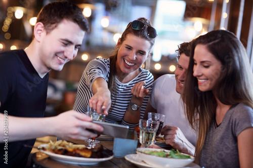 Obraz Group Of Friends Enjoying Meal In Restaurant - fototapety do salonu