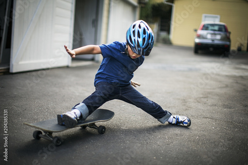 Young boy about to fall off his skateboard while playing on a residential driveway.