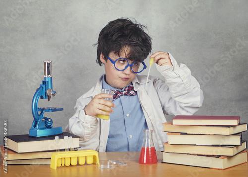 Fotografia  niño científico sobre fondo gris