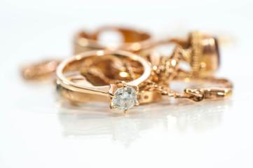 Prawdziwe złote pierścienie, łańcuchy, diamenty i klejnoty na błyszczącej powierzchni, białe tło.