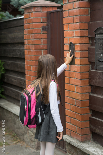 Foto  Little girl in school uniform ringing door bell