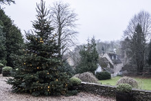 A Winter Garden, A Tall Pine Tree With Lights In The Branches, Christmas Decorations. A Traditional Stone Cottage With Slate Roof And Smoke Rising From The Chimney.