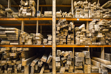 Large Selection Of Wooden Planks Stacked On Shelves In A Warehouse.
