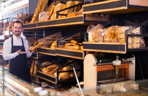 In de dag Bakkerij Male shop assistant demonstrating delicious loaves of bread in bakery