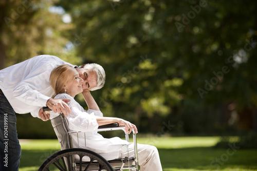 Senior man pushing his wife in a wheelchair.