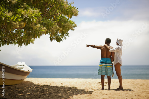 Couple standing on beach, husband is pointing at water.