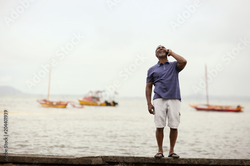 Laughing mature man talking on a cell phone next to a waterfront.