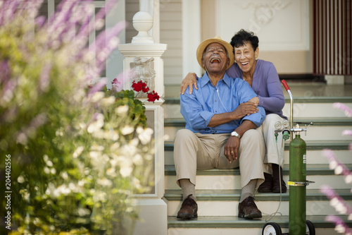 Senior woman sitting on the staircase and hugging her happy husband with nasal tubes.