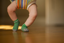 Legs Of A Baby On A Hardwood F...