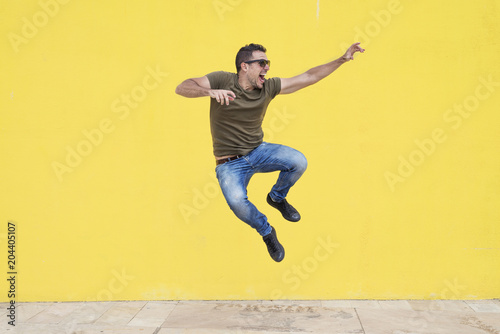 Fotografía  Young man with sunglasses jumping in front of a yellow wall.