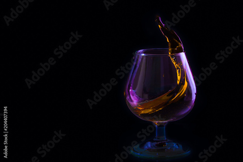 Staande foto Alcohol splash in a glass of brandy in colored lighting on a black background