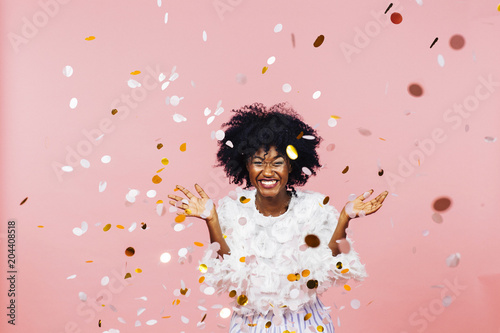 Fotografia  Celebrating happiness, young woman with big smile throwing confetti