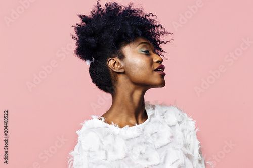 Profile portrait of a beautiful young woman with curly black hair, isolated on pink background